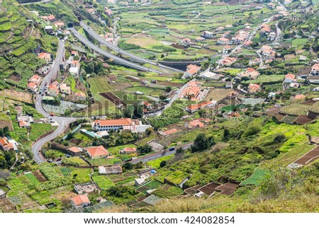 View down valley in Madeira Portugal.  High angle view down hillside into green valley with houses and roads in Madeira Portugal - stock photo