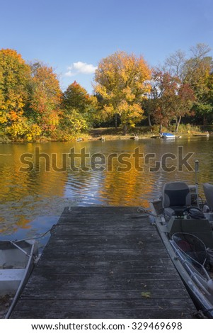 View from a boat dock on the lake with golden Autumn trees. - stock photo