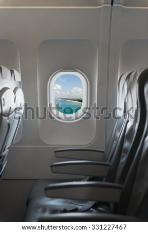 View from a commercial airplane cabin, blue sky and holiday destination, showing a row of comfortable chairs and armrests