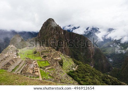 View from a distance with a hill to the ancient lost city of the Incas Machu Picchu, Peru, and the mountain valley in the misty and rainy weather