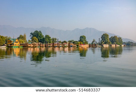 View from a far of Dal Lake shore with hotels as boathouse parked along the  in a blur background of mountain ranges during sunset, in Srinagar, Kashmir, India