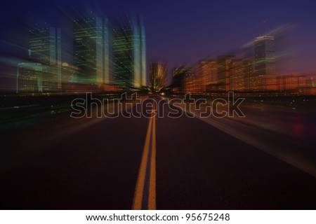 View from a vehicle traveling on a road at a high rate of speed into a modern city. The windows of the city highrises and skyscrapers reflect the early evening lighting and interior illumination. - stock photo