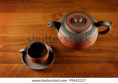 view from above at ceramic tea cup and kettle, standing on wooden table