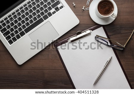 view from above. brown wooden office table with cup of coffee, notepad and laptop computer - stock photo
