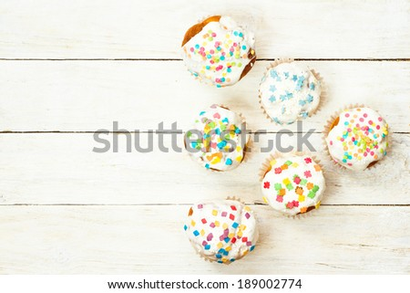 View from above Easter cupcakes on a white wooden background - stock photo