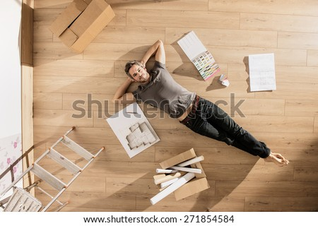 view from above, looking at the camera a modern man lying on the floor of his new home, there are blueprints and samples colors to help him to think about his new interior decoration