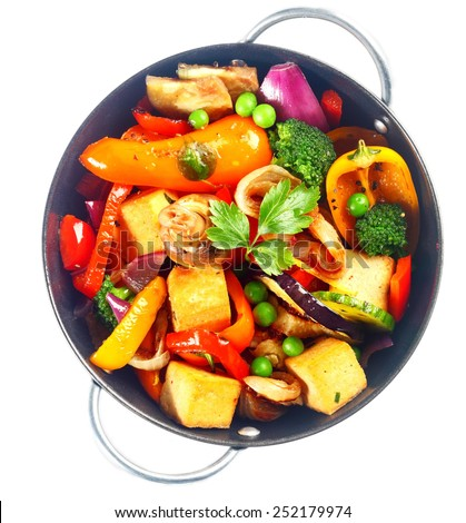 View from above of a bowl of delicious healthy bean curd, or tofu, and assorted fresh roast vegetables for vegetarian cuisine isolated on white - stock photo