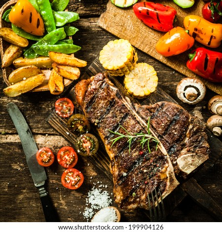 View from above of a delicious grilled porterhouse steak with assorted roast vegetables including tomato, peppers, mushrooms, corn, mangetout, and potato wedges