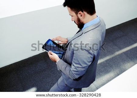 View from above of a smart University Professor reading electronic book on touch pad before lectures, prosperous man economist holding digital tablet with copy space screen for your text or content  - stock photo