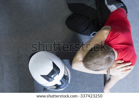 view from above of a young man with his helmet before starting a race in an outdoor go karting circuit - focus on the head - stock photo
