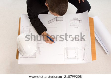 View from above of an architect drafting or modifying a building plan with his hardhat alongside - stock photo