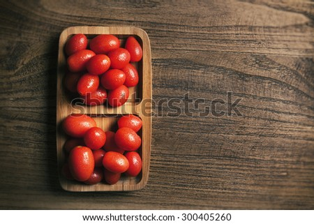 View from above of baby tomato on wood texture table - stock photo