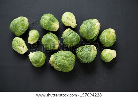 View from above of brussels sprouts over black wooden background - stock photo