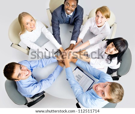 View from above of business team making pile of hands on working place - stock photo