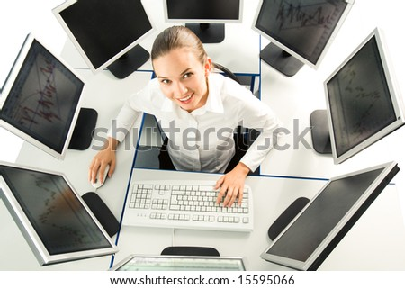 View from above of businesswoman sitting at desk with several computers around and looking upwards at camera - stock photo
