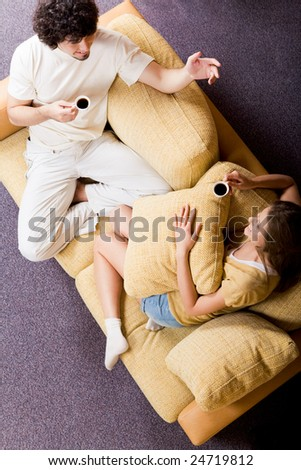 View from above of chatting couple sitting on sofa and drinking coffee in the morning