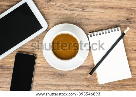 View from above of coffee cup with black smartphone, digital tablet computer, notebook and pencil on the wooden office desk table