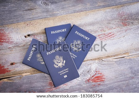 View from above of four United States passports on a rustic wooden table conceptual of family or group travel, with copyspace - stock photo