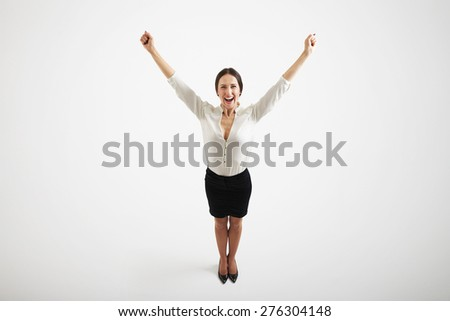view from above of smiley woman in formal wear raising her hands up over light grey background - stock photo
