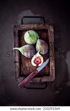 View from above of whole and halved ripe juicy fresh figs in an old vintage container in a rustic kitchen with a knife and copyspace - stock photo