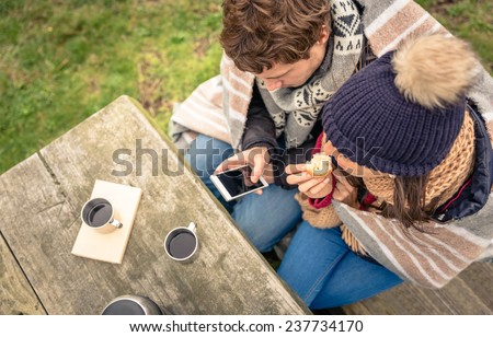 View from above of young beautiful couple under blanket looking smartphone and eating muffin in a cold day with sea and dark cloudy sky on the background - stock photo