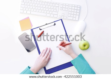 View from above of young businesswoman writing notes while sitting at office in front of computer.