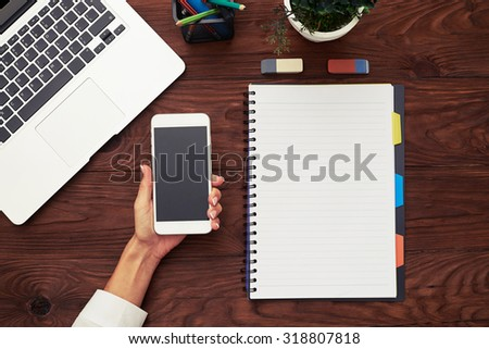 view from above on female hand holding smartphone over wooden table with laptop and empty notebook - stock photo
