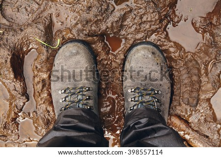 View from above on pair of trekking shoes in a mud