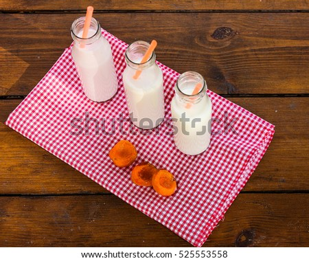 view from above. three glass bottles milkshake on a beautiful tablecloths and wooden background