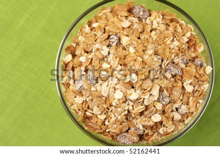 View from above to glass bowl with muesli on green cloth. - stock photo