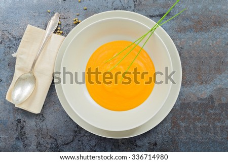 View from above to the delicious healthy pumpkin soup, spoon and napkin - stock photo