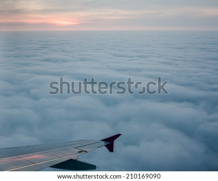 View from airplane to wings above clouds after sunset