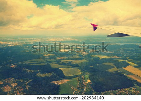 View from airplane window on fields and cities, image in retro colors