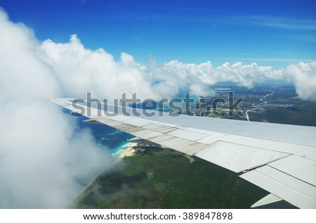 View from airplane window. Wing of an airplane flying above the clouds over tropical island - stock photo