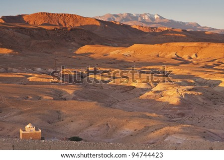 View from Ait Benhaddou on the High Atlas Mountains with a tomb of local saint called marabout in the foreground, Morocco - stock photo