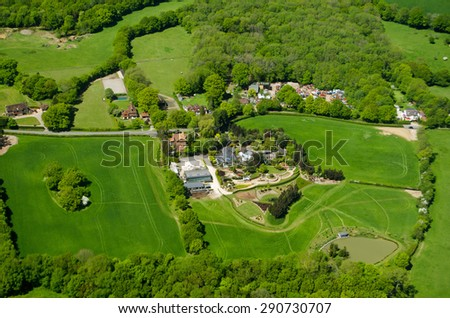 View from an airplane of expensive homes and farmland at Russ Hill in Surrey, close to Gatwick Airport in countryside.