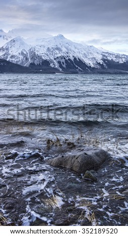View from an Alaskan beach in winter on a stormy day with snowy mountains in the background. - stock photo