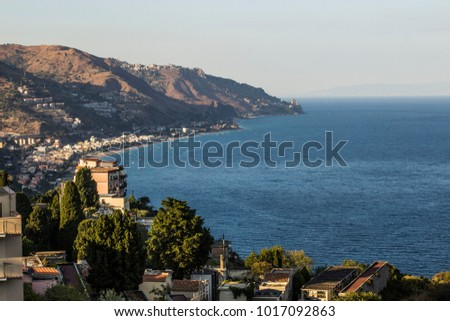 view from ancient town of Taormina in Sicily to the sea; amazing landscape view onto the Mediterranean sea from Taormina; romantic view in hot summer day