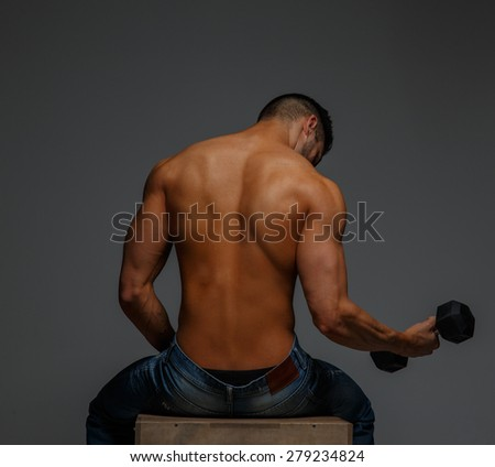 View from back of shirtless guy with dumbell on grey background - stock photo