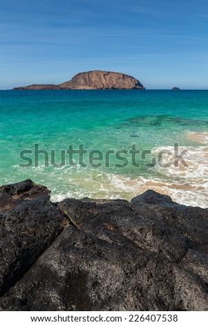 View from Baja de los Conchas in Isla Graciosa to Isla de Montana Clara, Canary Islands, Spain. - stock photo