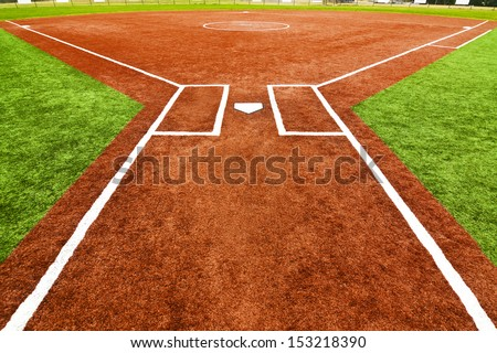 View from behind home plate looking towards the outfield across the pitcher�s mound with artificial turf field. The bright colors of the artificial turf are a high contrast to a normal playing field. - stock photo