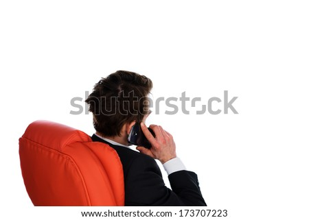 View from behind of a successful young businessman talking on a mobile phone while sitting back comfortably in a red office chair, isolated on white