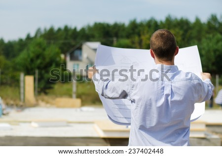 View from behind of a young architect or engineer checking a building plan on site holding it open in his hands as workmen work in the background - stock photo