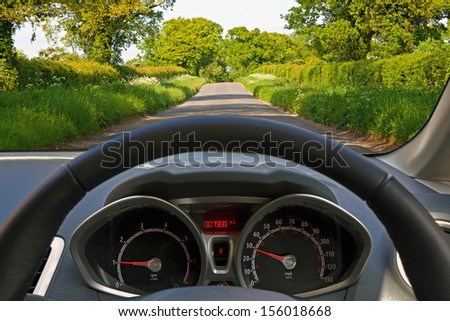 View from behind the steering wheel of a car whilst driving down a country road. - stock photo