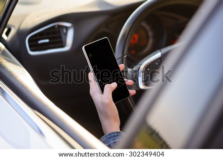 View from behind through the open window of a girl reading a text message as she drives along in her car with the blank screen visible to the viewer - stock photo