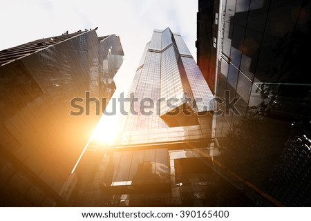 View from below of a tall skyscrapers in business district in sunny evening. Exterior of a modern office buildings in metropolitan city against beautiful sunset - stock photo