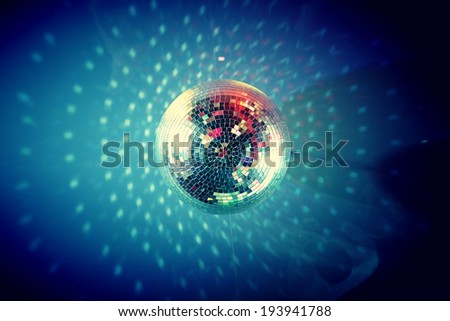 View from below of disco ball sparkling in darkness - stock photo