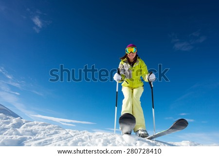 View from below of happy woman in mask  holding ski poles and ready to ski at Krasnaya polyana ski resort and Caucasus mountains in Sochi, Russia - stock photo