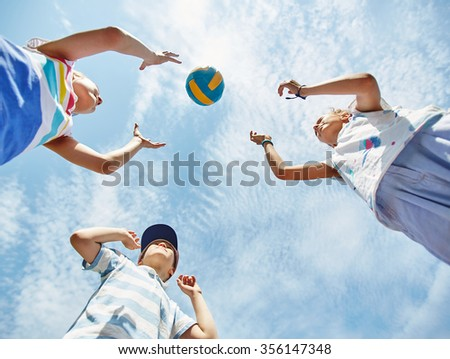 View from below of kids playing ball - stock photo