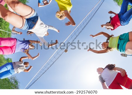 View from below of kids playing volleyball - stock photo